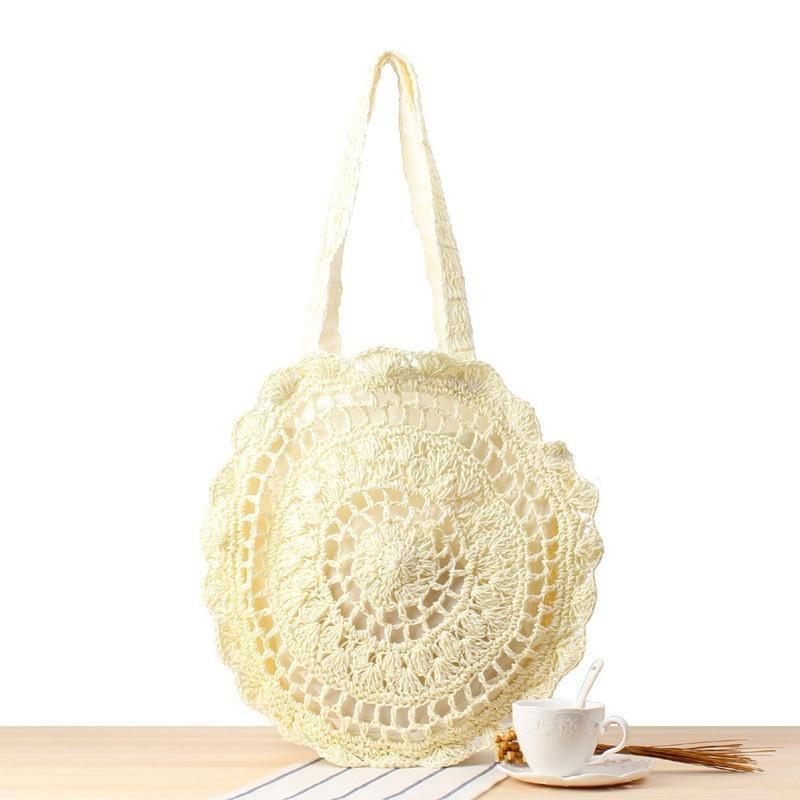 内側に裏地が付いた中空の丸い白いワンショルダーの手作りかぎ針編みバッグ